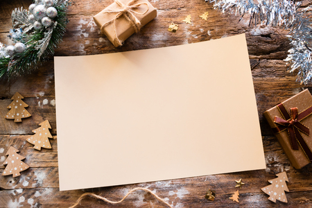 empty christmas letter with ornaments and gifts on a wooden background Stock Photo