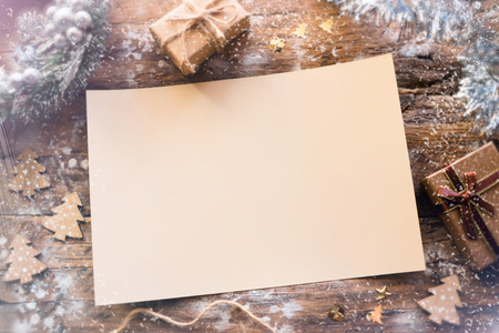 empty christmas letter with ornaments and gifts on a wooden background with bokeh and snow