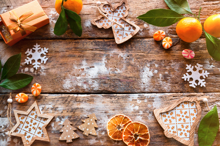 Frame from Christmas decorations and tangerine on a wooden background
