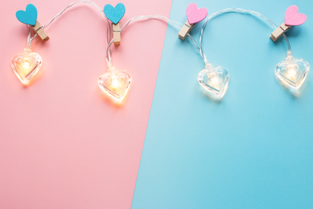 heart-shaped garlands and a place for text on a pink-blue background for Valentines Day