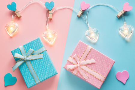 heart-shaped garlands and gifts on a pink and blue background for Valentines Day