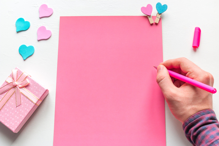 a man writes a congratulatory letter to a gift for Valentines Day