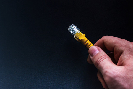 man holding a yellow network internet cable on a black background close-up with space for text