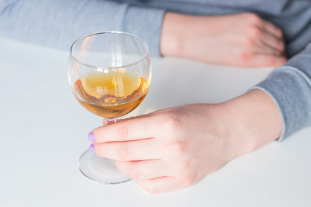 girl holding a glass with alcohol on a white background Stock fotó