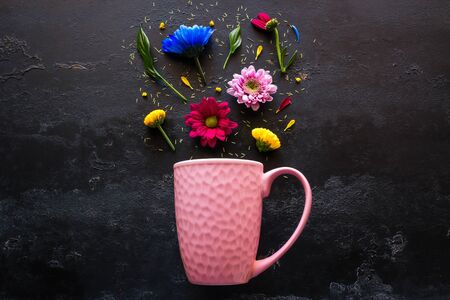 pink mug and a scattering of flowers and petals from it on a black background top view