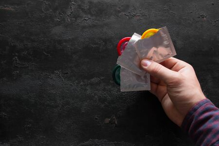 man holding a colored condom on a black background with space for text 写真素材