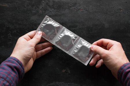 man holding a pack of condoms. concept contraception 写真素材