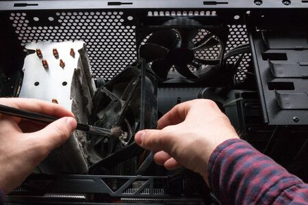 computer technician cleans the CPU cooler and hardware