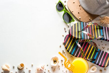 beach shoes, a baseball cap, glasses, juice and shells - beach accessories for summer holidays on a white background mockup Foto de archivo - 131825310