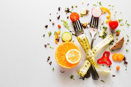 vegetables on forks with measuring tape on a white background with place for text. concept diet, weight loss, fat loss Reklamní fotografie