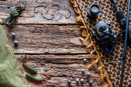 baits, hooks, fishing rod on the wooden background with space for text Foto de archivo - 131825479