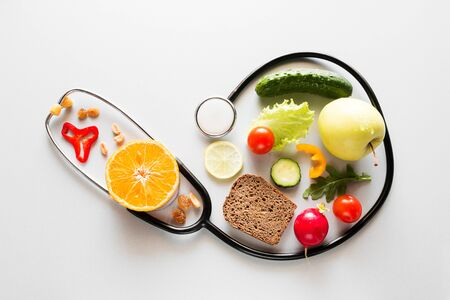fresh fruits and vegetables and stethoscope healthy eating concept Foto de archivo - 131827347