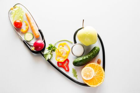 fruits and vegetables inside a stethoscope with heart shape diet vegetarian food concept Foto de archivo - 131826674