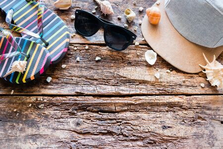 beach accessories on a wooden background with place for text. flip-flops, baseball cap, glasses, shells. summer vacation concept Foto de archivo - 133335564
