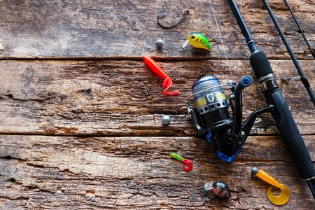 Kurgan, Russia-June 19, 2019 fishing tackle on a wooden background with space for text. spinning hooks silicone bait Foto de archivo - 131827472