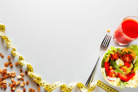 diet food and measuring tape with place for text on a white background concept slimming and healthy lifestyle Foto de archivo - 131825589