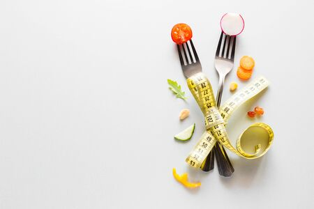 fresh vegetables on a fork and measuring tape on a white background with place for text concept healthy diet for weight loss Reklamní fotografie