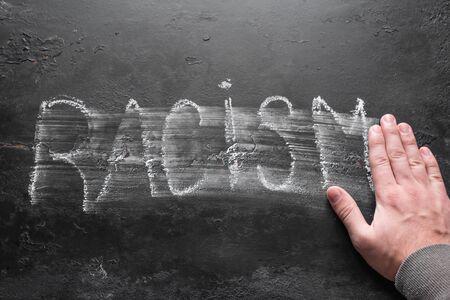 man erases the inscription racism concept stop racism selective focus
