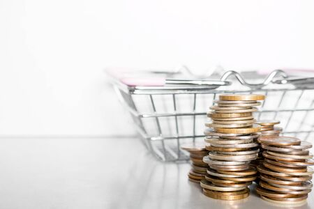 stack of coins and grocery cart on a white background with place for text concept for inflation, poverty, shopping Stock Photo
