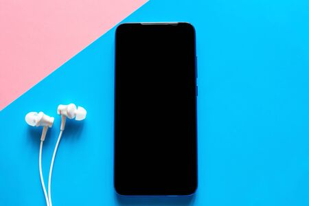 mobile phone on a colored background with a black blank screen and white headphones. smartphone with place for text mockup Stock Photo