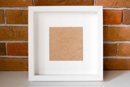 white photo frame on brick background mockup