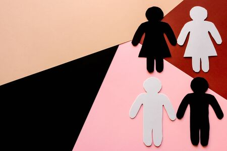Black and white cardboard silhouettes on a colored background. skin color discrimination concept