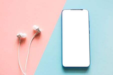 smartphone with a blank white screen and headphones on a colored background mockup Stock Photo