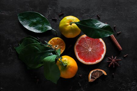 fresh and dry citruses with spices on a black background, strengthening immunity concept