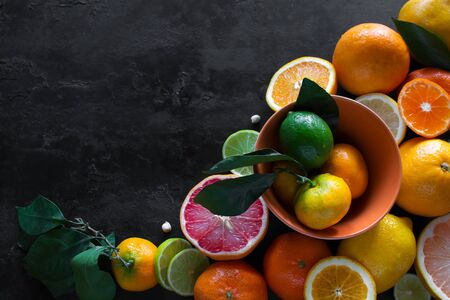 sliced fresh citruses grapefruits, tangerines and lime on a black background with place for text. vitamin c concept Stock Photo