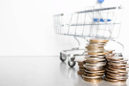 stack of coins and grocery cart on a white background with place for text concept inflation, poverty