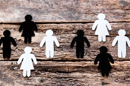 groups of white and black silhouettes on wooden background anti racism concept
