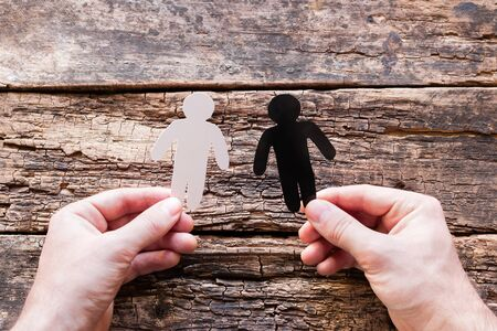 holding black and white silhouettes on wooden background stop racism concept