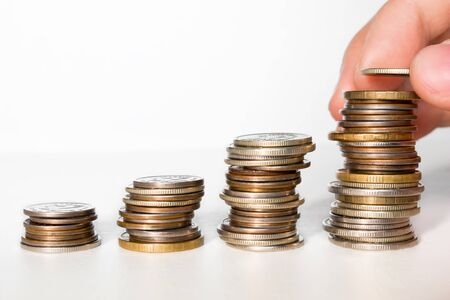 man puts a coin in a stack of coins, business growth concept close-up