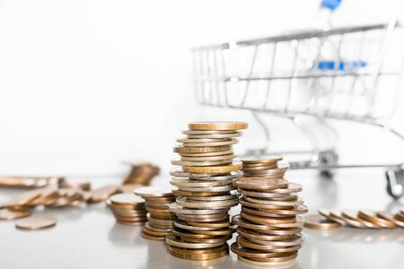 grocery cart and coins close-up on a white background