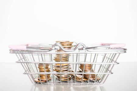 grocery basket with coins on a white background Stock fotó