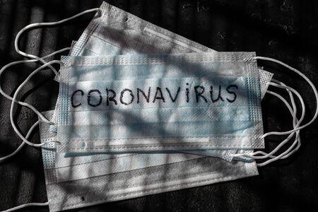 medical mask with the inscription coronavirus on a black background Zdjęcie Seryjne