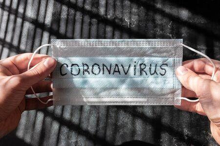 holding a medical mask with the inscription coronavirus Zdjęcie Seryjne