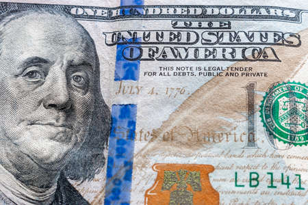 one hundred dollar bill and Franklin portrait close-up concept economic crisis