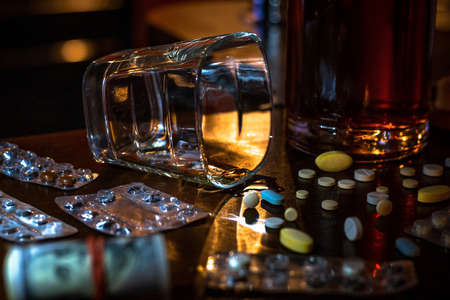 empty glass, alcohol, pills, drugs and money addiction concept