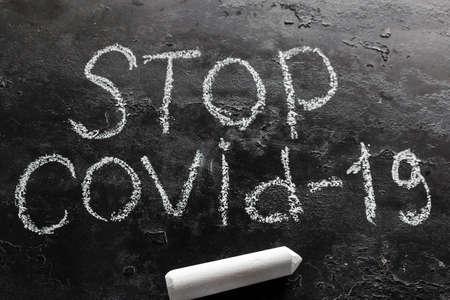 chalk inscription stop covid-19 on a black background