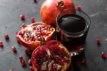 ripe pomegranate fruit and a glass with juice on a black background