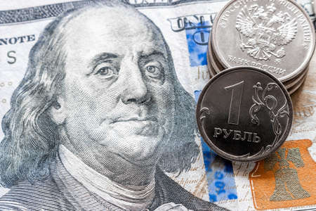 coins rubles on one hundred dollar bill close up concept economic crisis