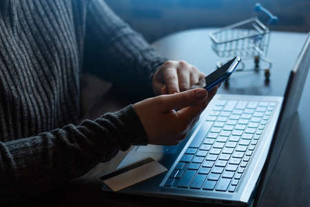 holding a smartphone on the background of a laptop and a bank card online shopping, payments concept Zdjęcie Seryjne