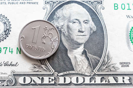 one ruble coin against the background of one dollar with a portrait of Washington