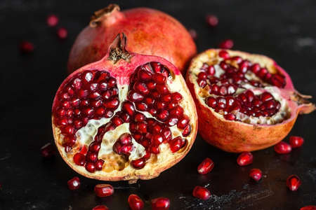 seeds of ripe pomegranate fruit close-up on a black background