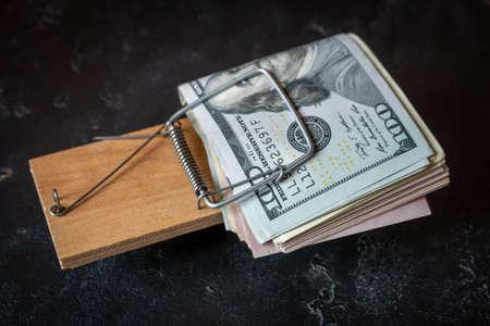 money trap on black background close up debt concept