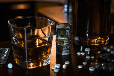money, pills, drugs and a glass of single malt whiskey concept bad habits, addiction