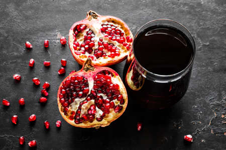 fresh pomegranate juice and pomegranate slices on a black background close-up