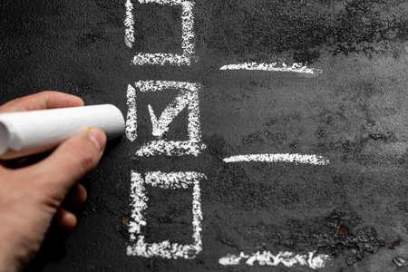 hand holds chalk and makes a choice. voting, checklist, option selection Zdjęcie Seryjne