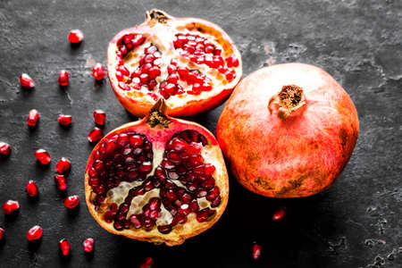 ripe pomegranate, slice and seeds on a black background